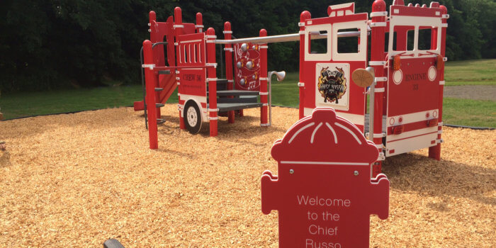 "Photo of playground modeled after a fire truck, with climbers, play panels, and a sign reading ""Wecome to the Chief Russo Playground""."