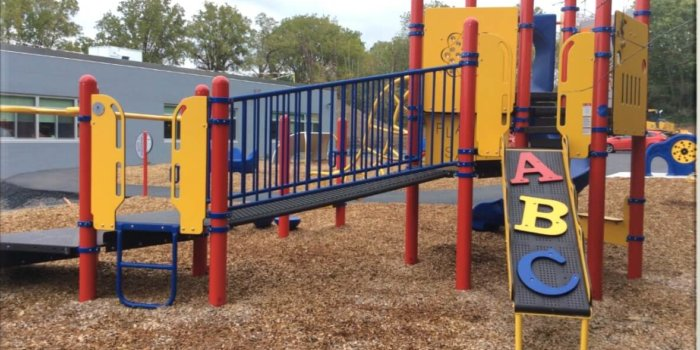 Photo of playground with ramp, climbers, slides, and play panels.
