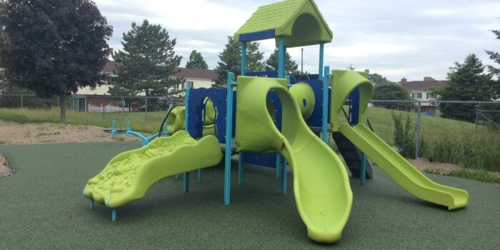 Photo of a small play structure with multiple slides and several climbers