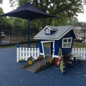 Photo of house-shaped play structure with shade umbrella