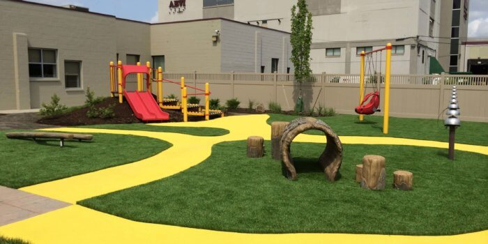 Photo of a play space that has a yellow path cutting through the grass, with a small play structure, a swing, and a log tunnel
