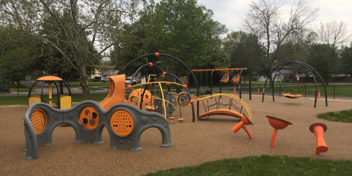 Photo of fully ADA compliant playspace, with poured-in-place rubber surfacing, sensory panels, play structures, and musical instruments