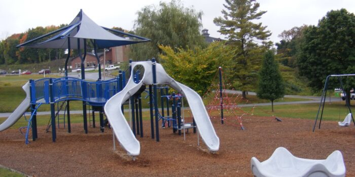 Photo of playground with slides, spinner, climbers, and decks.