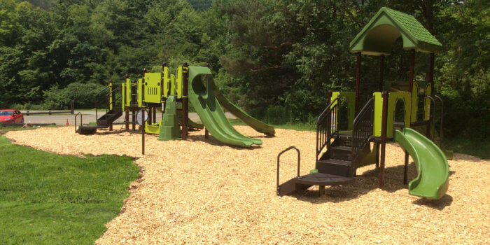 Photo of playground with slides, climbers, and multiple levels of decks.