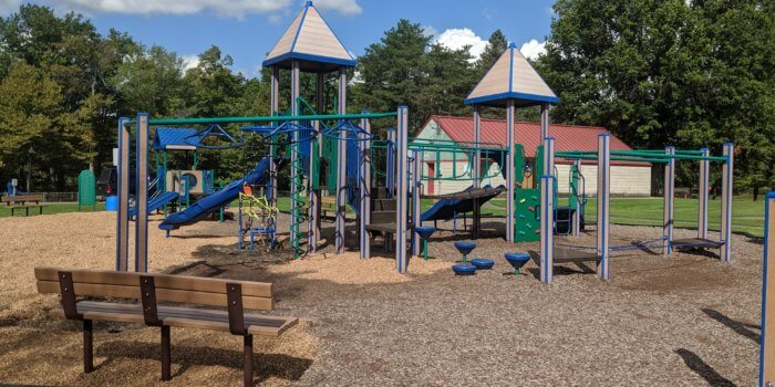Photo of playground with peaked roof, slides, climbers, and overhead play components.