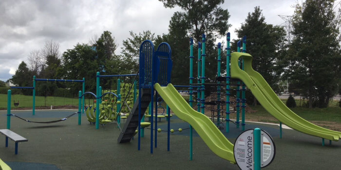 Photo of playground with multiple play structures, climbers, spinnesr, and swings