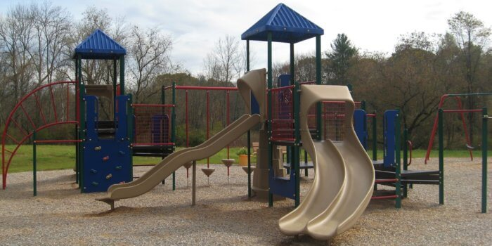 Photo of play structures with multiple slides, climbers, and swings