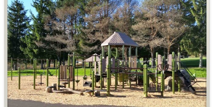 Photo of playground with climbers, slides, and decks.