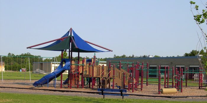 Photo of a large playground with multiple decks and strutures, as well as a large shade structure