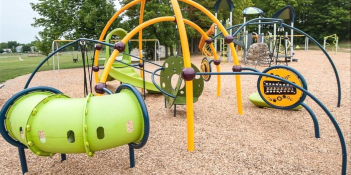 Photo of playground with curved climbing structure, swings, slides, climbers, and independent components.