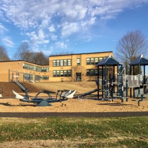Photo of play structures and a multi-user seesaw with the school in the background