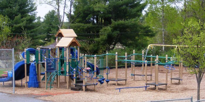 Photo of a large playground with multiple structures and an independent swing set