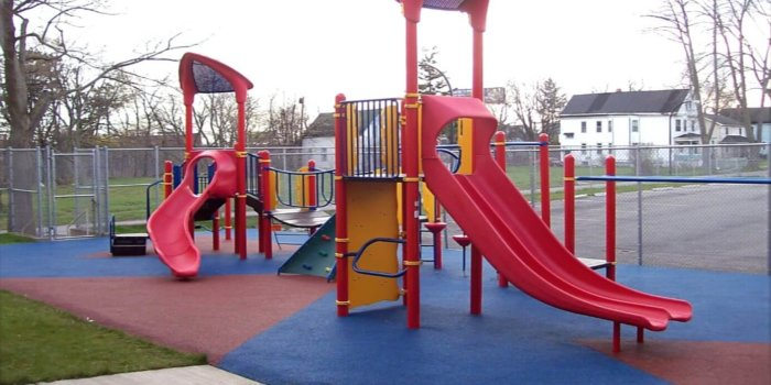 Photo of playground with slides, climbers, bridge, and poured in place rubber surfacing.