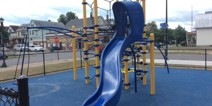 Photo of a tall play structure with cables and slide