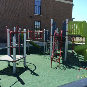 Photo of a play structure with climbers, multiple decks, and a slide