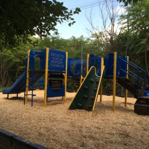 Photo of a playground with several decks, climbers, and slide
