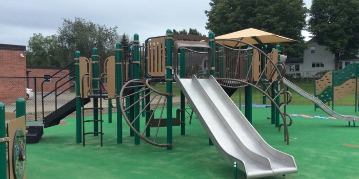 Photo of a playground with multiple decks, slides, and climbers, and durable carpeting installed as a safety surface