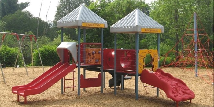 Photo of playground with swings, rope climbing net, slides, and play panels.