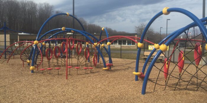 Photo of playground with climbing nets, overhead ladders, and other climbers.