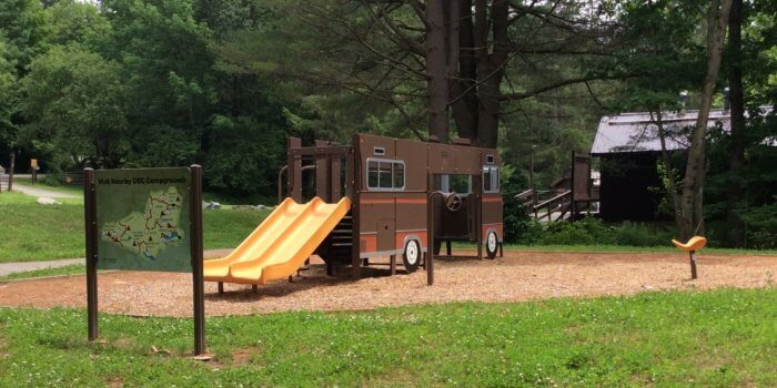 Photo of RV shaped play structure with a slide and independent spinner.