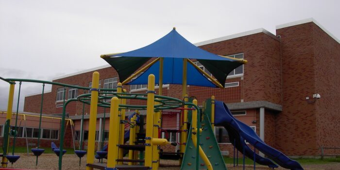 Photo of a play structure with numerous connecting climbers and steps, covered by a large single post shade structure