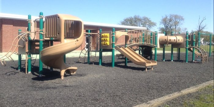Photo of playground with multiple play structures, each with slides and climbers.
