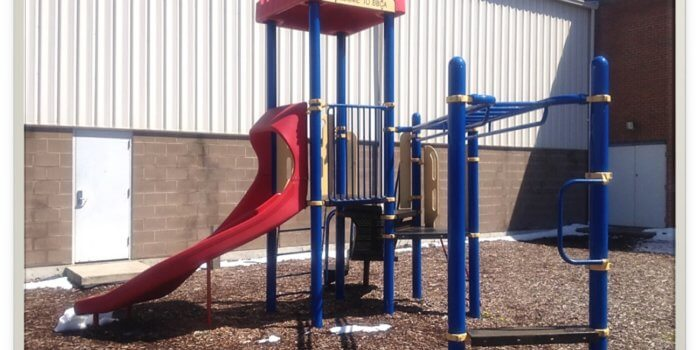 Photo of small play structure with slide, roof, and climbers.