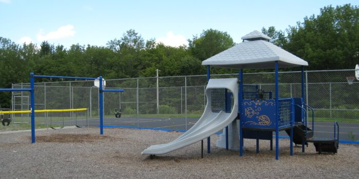 Photo of a small play structure and swings