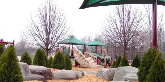 Photo of playground with climbers, slides, CoolTopper shades, and landscaped trees and boulders.