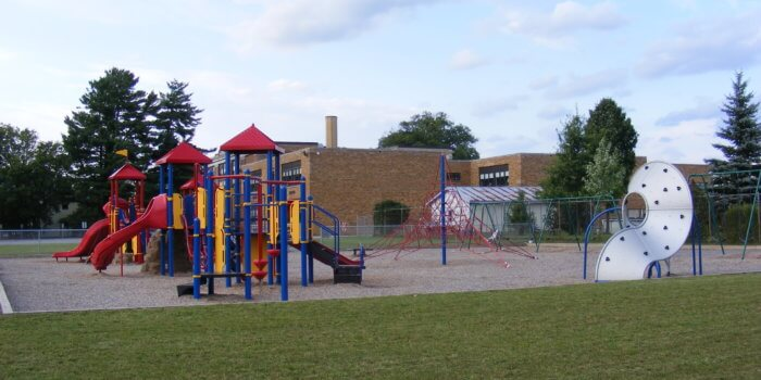 Photo of multiple play structures with slides and climbers and a large rope climbing structure