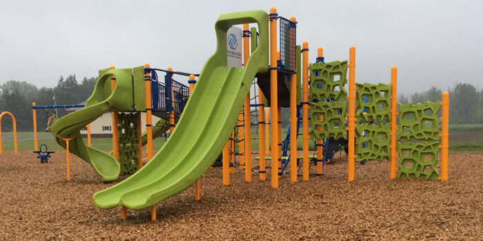 Photo of a play structure with multiple poles, connected decks, slides, and climbers, as well as an independent swingset