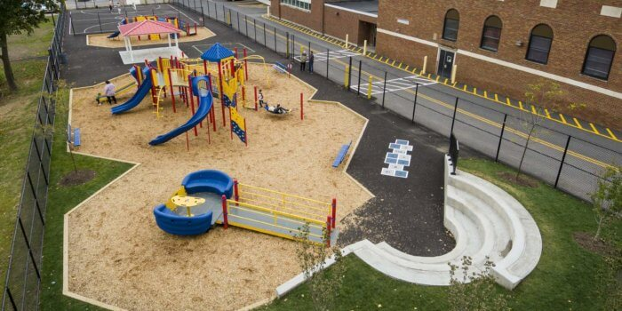 Photo of a large playground area with multiple structures and bench seating built into the topography