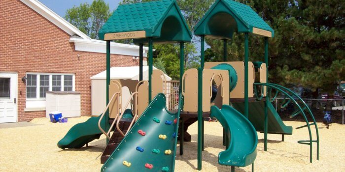 Photo of a play structure for 2-5 year olds with roofs, slides, and climbers