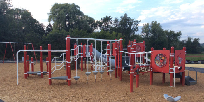 Photo of a playground with multiple connected decks, climbers, slides, and swings