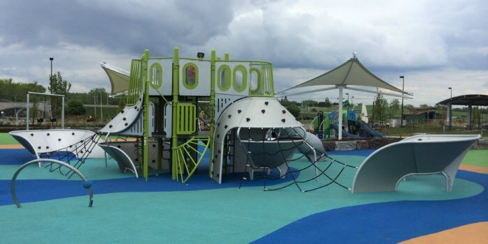 Photo of a futuristic, ship-inspired play structure, with poured-in-place rubber surfacing colored to resemble a shore