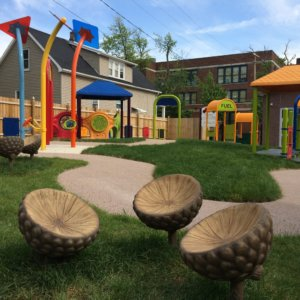Photo of acorn-shaped seats, with play equipment in the background