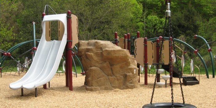 Photo of a tire swing and play structure, featuring a rock shaped climber, slides, and arching posts with play components attached