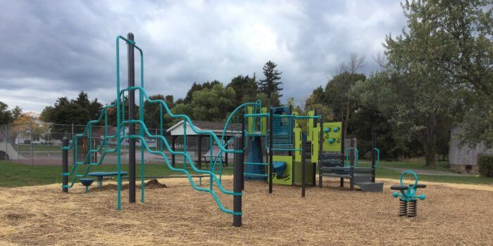 Photo of playground with slides, climbers, play panels, and independent play components.