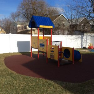 Photo of a small play structure in primary colors with decks, a slide, and a tunnel