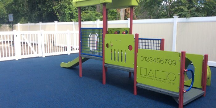 Photo of a small play structure in with decks, a slide, and a tunnel on unitary surfacing