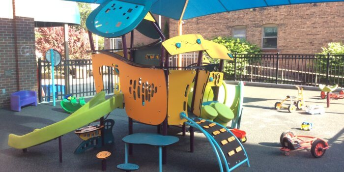 Photo of a shaded play structure for 2-5 year olds with climbers, a slide, and interactive play panels