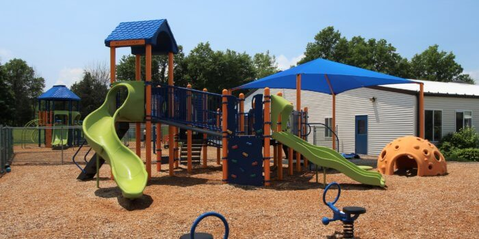 Photo of a large play structure with multiple slides and climbers, with independent components, a shade structure, and more play equipment around it