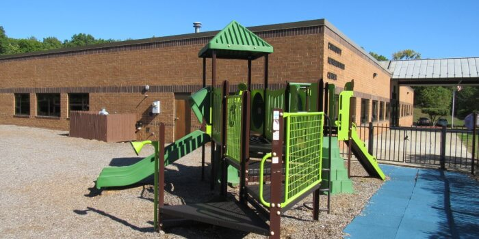 Photo of a small play structure with slides, climbers, panels, and talk tubes.