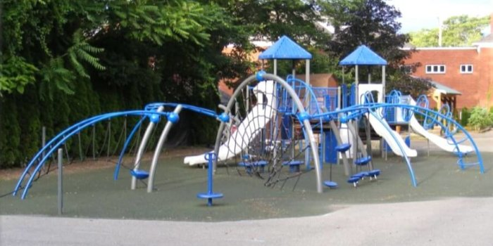Photo of playground with climbing nets, slides, decks, and climbers.
