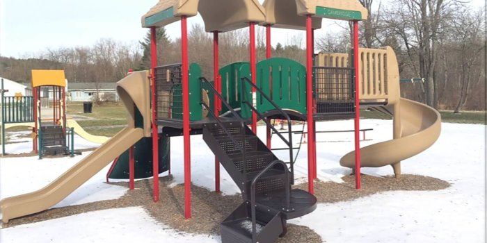 Photo of playground with climbers, slides, and covered decks.