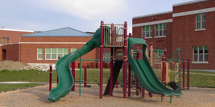 Photo of a play structure with multi-level decks, slides, and climbers