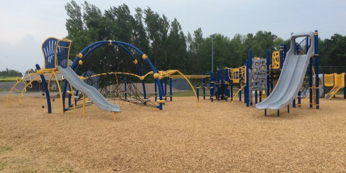 Photo of playground with slides, climbers, decks, and climbing net.
