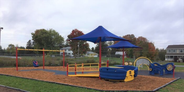 Photo of a playground with a mix of poured-in-place rubber surfacing and wood fiber, featuring a wheelchair accessible glider, a swingset, sensory panels, and outdoor music instruments