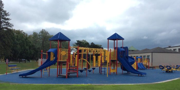 Photo of playground with slides, climbers, see saw, and play panels.