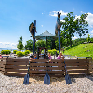 Photo of a boat shaped play structure with faux oars and a sail